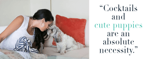 """girl reaching out to kiss her dog sitted on the sofa with an orange throw pillow at its back, with the saying """"cocktails and cute puppies are an absolute necessity"""" beside the image."""